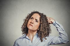 woman scratching head thinking daydreaming about something wondering - stock photo