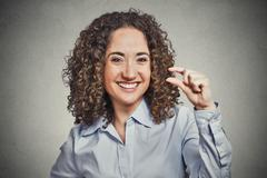 funny young woman showing small amount size gesture with hand - stock photo