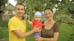 Happy family playing in the garden with the baby. Mom, dad, son, smile and laugh - stock footage