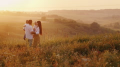 The couple gently kissing, holding his two sons. Meet the sunrise sun Stock Footage