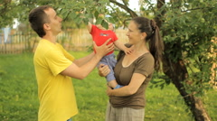 Happy family playing in the garden with the baby. Mom, dad, son, smile and laugh Stock Footage