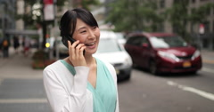 Young Asian woman in city street happy talking on cell phone - stock footage