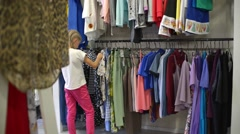 Child Girl with Pigtails Get Shopping at the Clothes Store Stock Footage