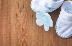 close up of baby bootees and soother for newborn - stock photo