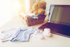 close up of baby clothes, toys and laptop at home - stock photo