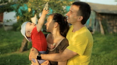 Happy family playing in the garden with clothespins. Mom, dad, son, smile and Stock Footage