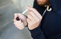 close up of addict smoking marijuana joint - stock photo