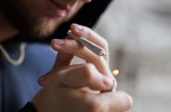 close up of addict lighting up marijuana joint - stock photo