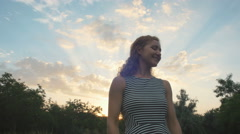 Young woman walking in park during sunset Stock Footage