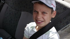 Boy sitting on the back seat of a car wearing a seat belt Stock Footage