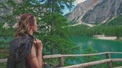 Woman hiker walking along the road near Lago di Braies, Italy Stock Footage