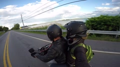 Passenger on motorcycle films their ride along water Stock Footage