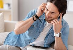 Delighted handsome man listening to music - stock photo