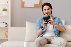 Positive smiling man playing video games - stock photo