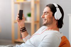 Positive man listening to music - stock photo