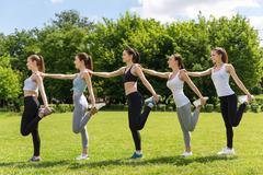 Cheerful women doing sport activities in the park Stock Photos