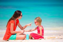 Mother applying sun protection cream to her daughter at tropical beach Stock Photos