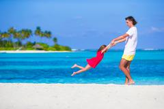 Little cute girl and dad during tropical beach vacation Stock Photos