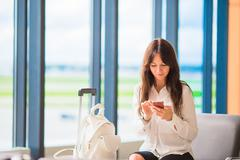 Female passenger in an airport lounge waiting for flight aircraft. Silhouette of - stock photo