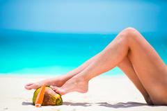 Slim woman applying sunscreen on her legs, sitting on sandy beach with sea Stock Photos