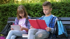 Teen cute boy and gir reading book sitting on bench at park Stock Footage