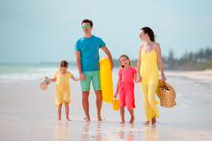 Young family of four on beach vacation Stock Photos