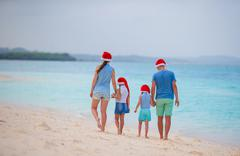 Happy family with two kids in Santa Hats on summer vacation. Christmas holidays Kuvituskuvat