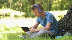 Teen boy 12-14 year old in headphones with tablet.  Stock Footage