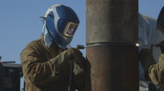 Worker welding a foundation pile while a concrete truck passes behind him Stock Footage