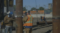 Construction workers welding foundation pile Stock Footage