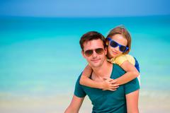 Little girl and dad during tropical beach vacation Stock Photos
