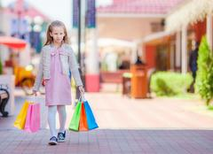 Adorable smiling little girl with shopping bags in big mall Stock Photos