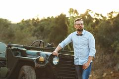 Young stylish man with glasses and bow tie near the old-fashioned SUV - stock photo