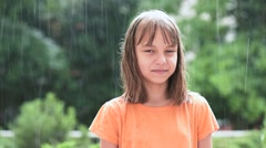 Little girl having fun playing in the rain - stock footage