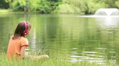 Girl with tablet pc listening to music or  video in summer park at lakeside Stock Footage