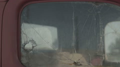 Broken windshield on truck with bullet holes - stock footage