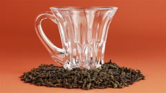 Tea being poured into glass tea cup on brown background Stock Footage