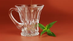 Tea being poured into glass tea cup and mint leaves on brown background Stock Footage
