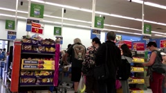 People line up for paying foods at check out counter inside Walmart store Stock Footage