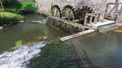 4K. Old water mill still working. Wooden wheels are rotating. Slovenia. Stock Footage