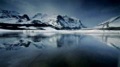 Lake with Ice reflecting snow covered mountains, Banff NP, Canada Stock Footage