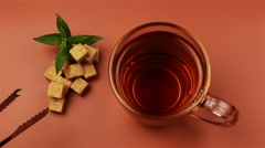 Sugar cubes added into tea glass on brown background Stock Footage