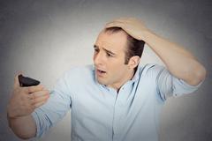 Shocked man feeling head, surprised he is losing hair Stock Photos