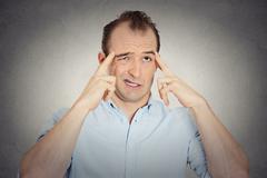 headshot young businessman thinking trying hard to remember something - stock photo