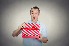 Happy super excited surprised young man about to open unwrap red gift box Stock Photos