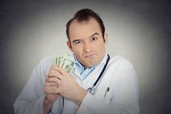 Grumpy greedy miserly health care professional holding money Stock Photos