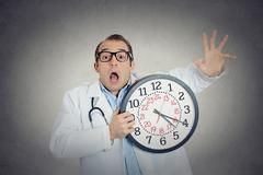 Busy, unhappy male health care professional, funny looking doctor Stock Photos