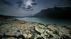 Lichen on rocks with lake in background, Glacier NP, MT Stock Footage