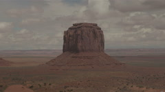 An iconic Monument Valley butte rises from the valley floor Stock Footage