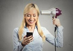 woman reading news on smartphone holding hairdryer - stock photo